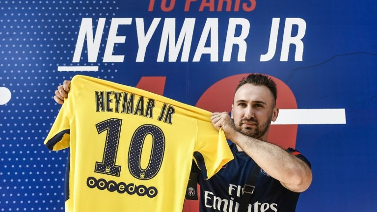 A PSG fan holds a PSG yellow away jersey, marked with the number 10 and the name of Brazilian star Neymar, after he purchased it from the Paris-Saint-Germain soccer club store on the Champs Elysees avenue in Paris on August 4, 2017. (AFP Photo/Philippe Lopez)