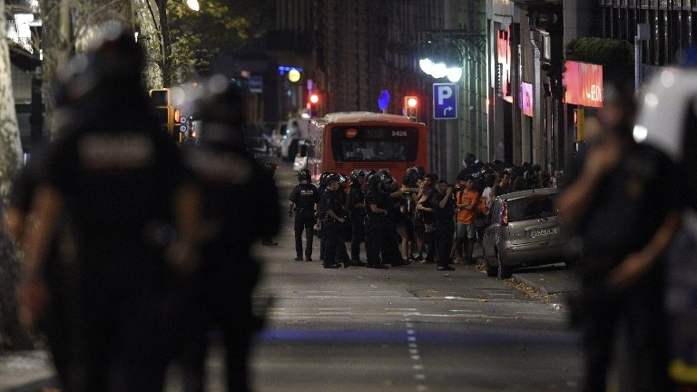 Spanish policemen gather in a cordoned off area after a van plowed into the crowd, killing 13 persons and injuring over 80 on the Rambla in Barcelona on August 17, 2017. (AFP PHOTO / LLUIS GENE)