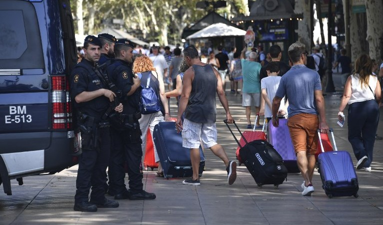 Spanish policemen stand guard as tourists pass by with their suitcases on the Rambla boulevard on August 18, 2017 a day after a van ploughed into the crowd, killing 13 persons and injuring over 100 on the Rambla in Barcelona. (AFP PHOTO / Pascal GUYOT)