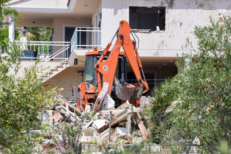 A picture taken on August 20, 2017 shows a crane in the rubble of a house,where suspects of this week's twin assaults in Spain were believed to be building bombs, in Alcanar. (AFP PHOTO / JOSE JORDAN)