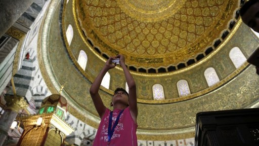 A Palestinian boy from the Gaza Strip takes a photo inside the Dome of the Rock mosque in the Al-Aqsa mosque compound in Jerusalem's old city on August 20, 2017 as he visits the city for the first time as part of an exchange program run by the UN agency for Palestinian refugees. (AFP PHOTO / AHMAD GHARABLI)