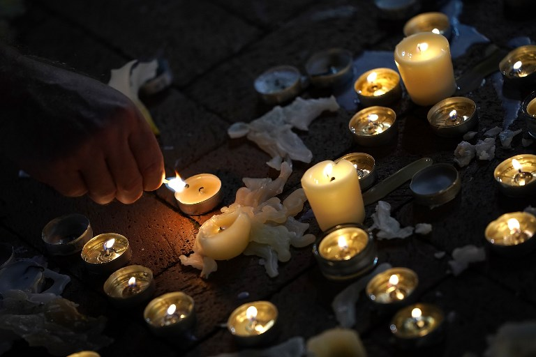 A man tends a makeshift candlelight vigil for those who died and were injured when a car plowed into a crowd of anti-fascist counter-demonstrators marching near a downtown shopping area August 12, 2017 in Charlottesville, Virginia. (Win McNamee/Getty Images/AFP)