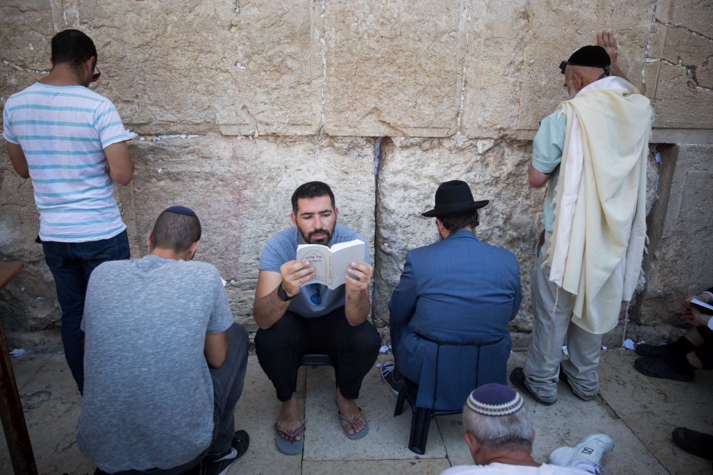 Jewish men pray as they gather for the ritual of Tisha B'Av at the Western Wall in the Old City of Jerusalem, Photo by: JINIPIX
