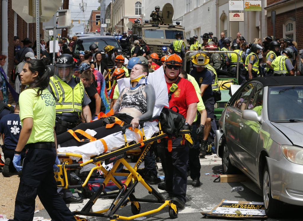 Rescue personnel help injured people after a car ran into a large group of protesters after a white nationalist rally in Charlottesville Virginia