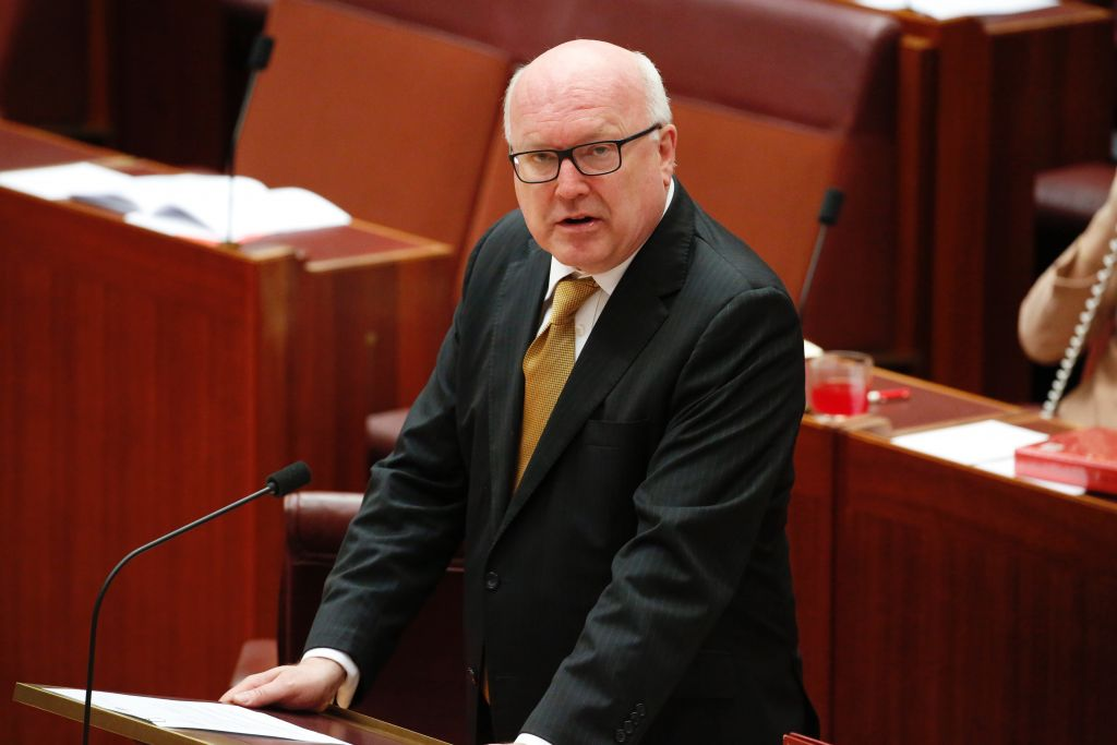 Attorney-General George Brandis stands to chastise an Australian senator who provoked an angry backlash from lawmakers by wearing a burqa in Parliament House in Canberra, Australia, Thursday, Aug. 17, 2017. .(Jed Cooper/Australian Broadcasting Corp. via AP)