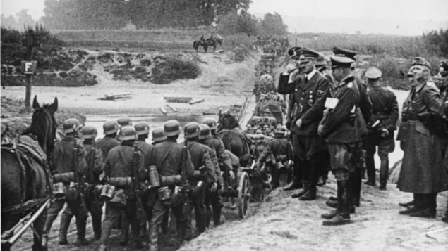 Hitler watching German soldiers marching into Poland in September 1939.