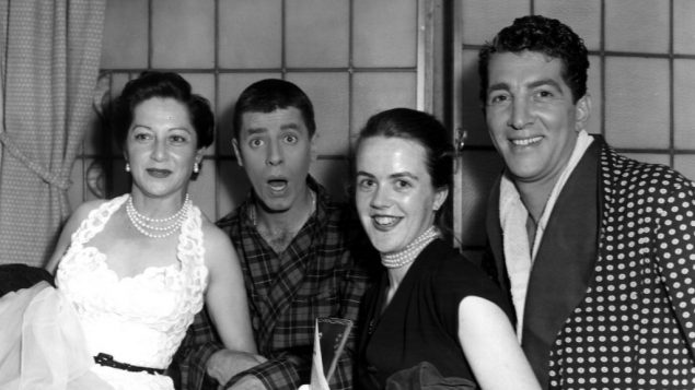 American singer and actor Dean Martin (1917 - 1995) and a clowning Jerry Lewis stand with Mrs Val Parnell and Mrs Clodagh Haherty.