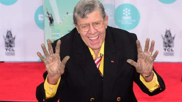 US comedian Jerry Lewis shows his hands at his Hand and Footprint ceremony at the TCL Theater in Hollywood, California on April 12, 2014. He is best known for his slapstick humor in film, television and stage