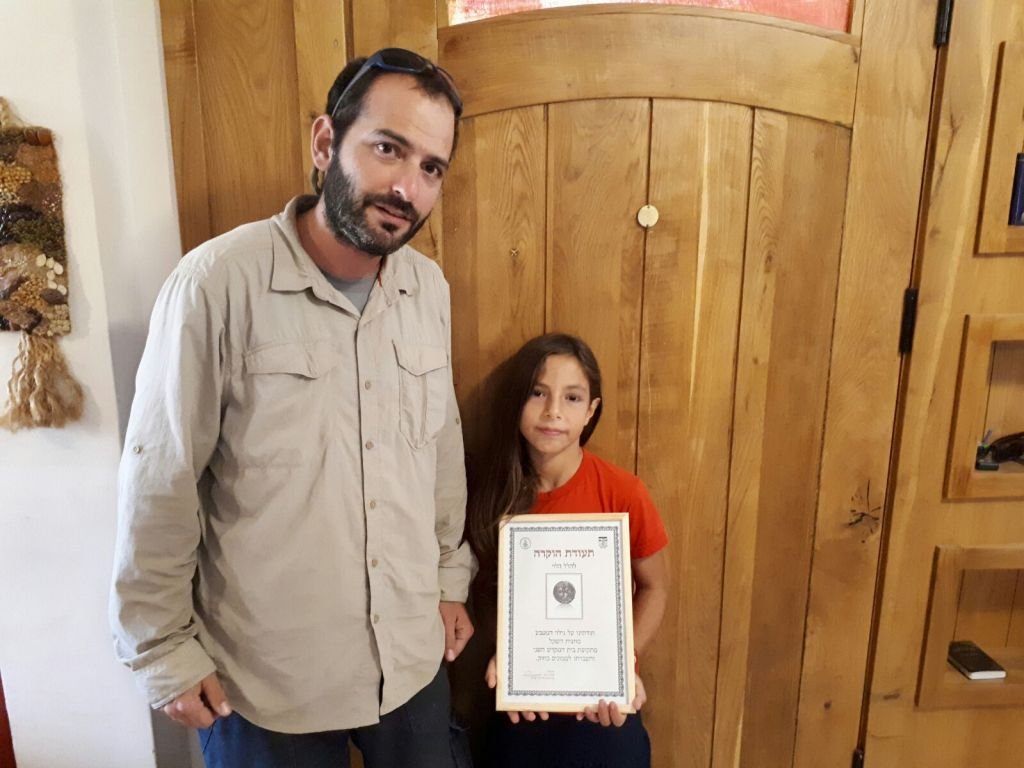 8-year-old Hallel Halevy with the Civil Administration archaeologist who collected the '2,000-year-old half-shekel' coin from her home in Halamish, August 23, 2017. (courtesy)