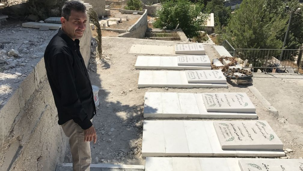 Hassan Dabash stands at the graves of his ex-wife and five children who were killed in a car accident in the West Bank on June 27, 2017. (Jacob Magid/Times of Israel)