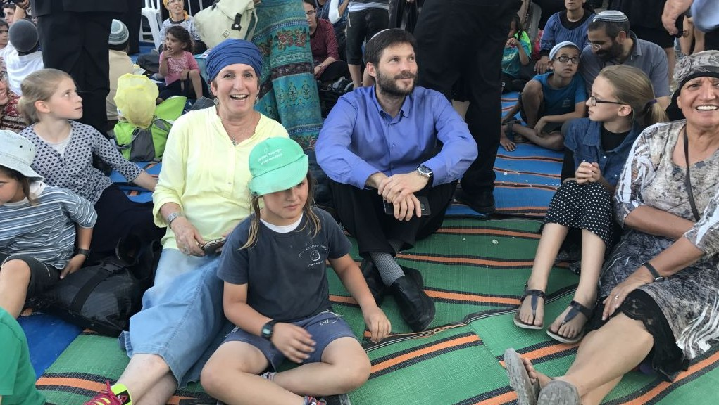 Jewish Home MK Bezalel Smotrich (blue shirt) sits among the hundrds who gathered for a ceremony at the evacuated Sa-nur settlement in the northern West Bank. (Jacob Magid/The Times of Israel)