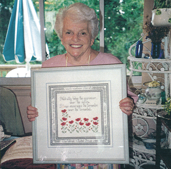 Betty Samuels holds one of her works, which spells out some of her beliefs.