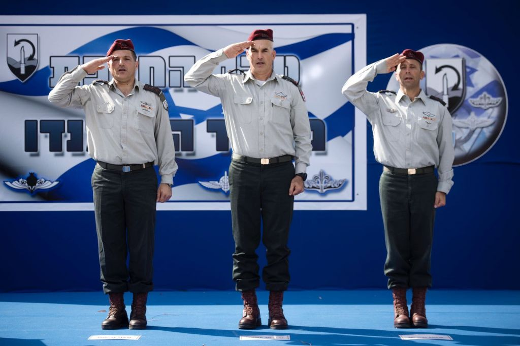 From left, Col. David Zini, Brig. Gen. Uri Gordin and Col. Avi Blot salute during a ceremony naming Blot the new head of the army's Commando Brigade on August 17, 2017. (Israel Defense Forces)