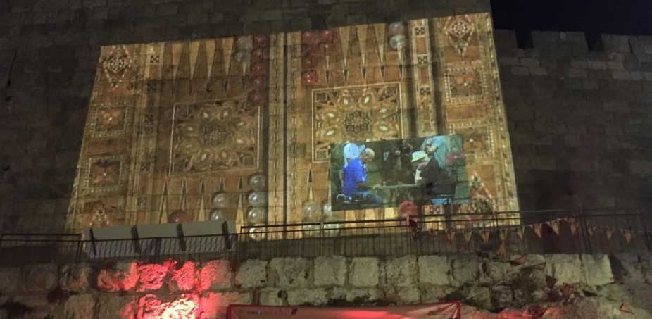 The final game of the first Jerusalem Backgammon Championship is beamed onto the Old City walls (Times of Israel staff)