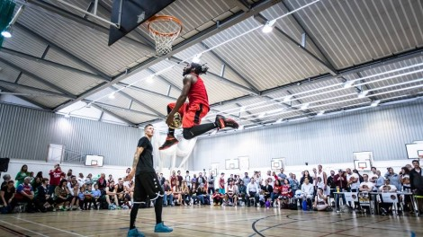 Spectators watch on, as a participant in the George Goldstone Charity tournament slam dunks the ball