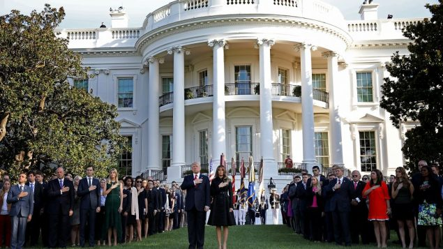US President Donald Trump, US first lady Melania Trump and others participate in a moment of silence on the South Lawn of the White House during a memorial service for the 9/11 terrorist attacks September 11, 2017 in Washington, DC.