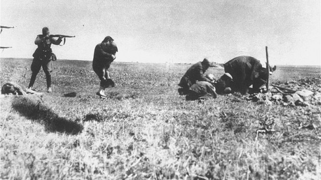 Einsatzgruppen members killing Jews in Ivanhorod, Ukraine, 1942. A woman is attempting to protect a child with her own body just before they are fired upon with rifles at close range.
