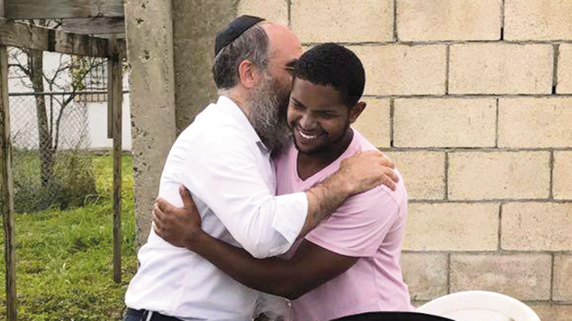 Rabbi Zarchi and a Puerto Rican hurricane survivor share a hug.