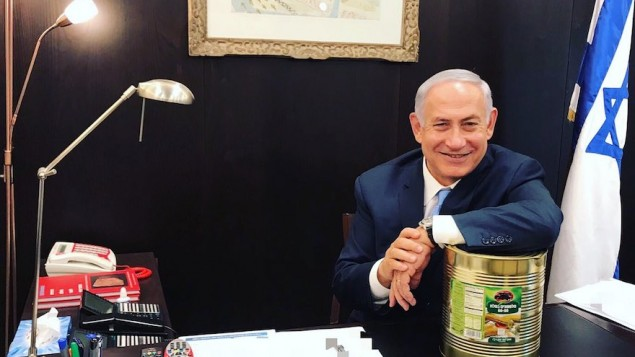 Prime Minister Benjamin Netanyahu posing with a large can of pickles, Oct. 23, 2017. (Courtesy of Prime Minister's Office) Via JTA