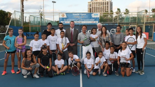 Sir Cliff (centre) plays a tennis racket like it's a guitar, surrounded by Jewish and Arab kids