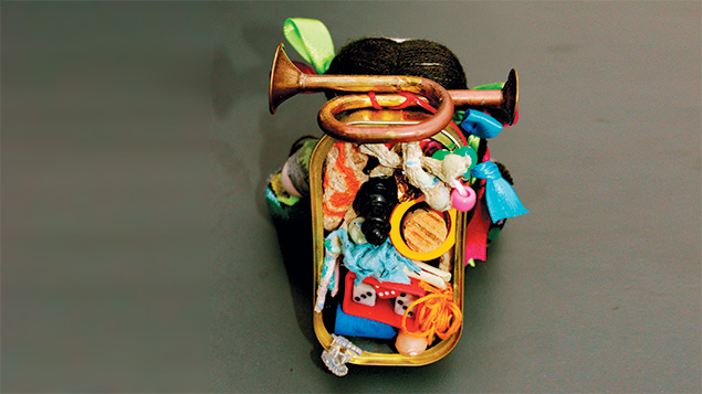 This figure, made of Mexican handcrafted bits, is carrying a sardine-can backpack.