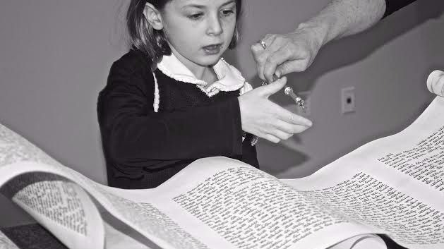Young girl interacting with Torah scroll, courtesy of JOFA Archives