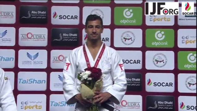 Tal Flicker on the podium with the International Judo Federation uniform, as he quietly sings Hatikvah