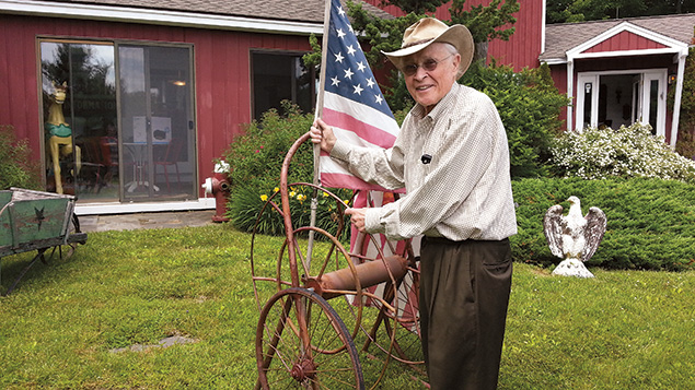 Dr. Scherl places an American flag on a lawn ornament at his home in Englewood Cliffs.