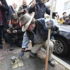 """Artist Gunter Demnig lays four """"Stolpersteine"""" (stumbling blocks) for Karolina Cohn and her family in Frankfurt, Germany, Monday, Nov. 13, 2017. Relatives participated in a memorial ceremony for Karolina Cohn, a Jewish girl from Frankfurt who perished in the Holocaust more than 70 years ago. The story of her life and death had been all but erased by the Nazis, until archeologists last year unearthed a silver pendant engraved with her birth date and birthplace at the grounds of the former Sobibor death camp. (Arne Dedert/dpa via AP)"""