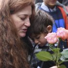 """Mandy Eisemann from Dickerson, Maryland. with her son Levi (4), relatives of the Cohn family, places flowers at four """"Stolpersteine"""" (stumbling blocks) for Karolina Cohn and her family in Frankfurt, Germany, Monday, Nov. 13, 2017. Relatives participated in a memorial ceremony for Karolina Cohn, a Jewish girl from Frankfurt who perished in the Holocaust more than 70 years ago. The story of her life and death had been all but erased by the Nazis, until archeologists last year unearthed a silver pendant engraved with her birth date and birthplace at the grounds of the former Sobibor death camp. (Arne Dedert/dpa via AP)"""