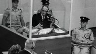 Nazi war criminal Adolph Eichmann stands in a protective glass booth flanked by Israeli police during his trial June 22, 1961 in Jerusalem. (Photo by GPO)