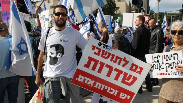 "Im Tirtzu activist holding a sign reading ""The residents of Sderot also have Human Rights"""