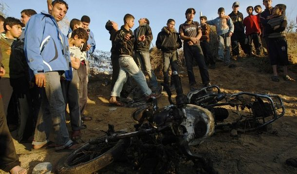 Palestinians gather around a destroyed motorcycle after an Israeli air strike in Khan Younis