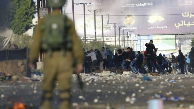 Palestinians clash with Israeli troops during a protest against U.S. President Donald Trump's decision to recognize Jerusalem as the capital of Israel in the West Bank City of Nablus, Friday, Dec. 8, 2017. (AP Photo/Majdi Mohammed)