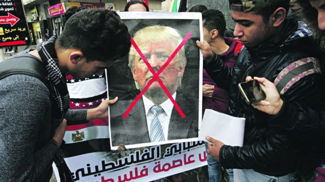Arab protesters hold a sign with a picture of Donald Trump crossed out, in opposition to the President's move