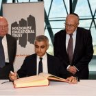 Holocaust survivors Ben Helfgott and Manfred Goldberg  besides Mayor of London​ Sadiq Khan​, as he signs the Holocaust Educational Trust (UK)​ Book of Commitment at City Hall.