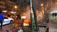 An overturned bin is set alight in a Tehran street, as demonstrations across the Islamic Republic spread during the new year period.