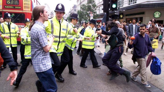 Police lead away a protester outside in central London calling for an end to the sale of goods from Israeli settlements.