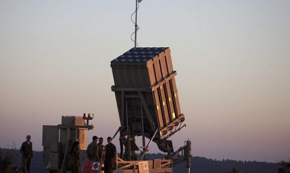 Israeli soldiers walk by an Iron Dome missile defense system deployed near Jerusalem, September 2013.