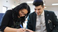 Reuben signing on the dotted line, with his mum