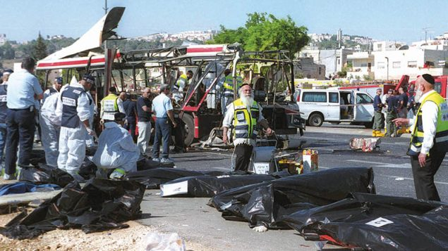 Israeli rescue workers stand over victims' bodies at the scene of a Palestinian suicide bombing on a passenger bus in Jerusalem on June 18, 2002.