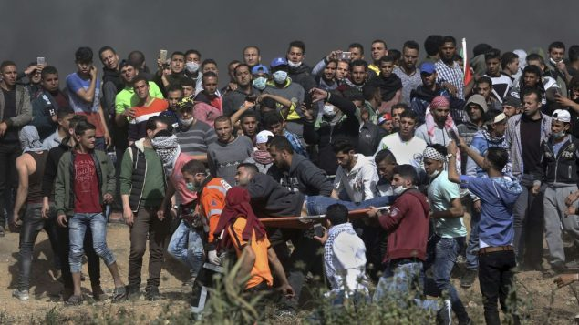 Palestinian protesters carry a wounded man from during a protest at the Gaza Strip's border with Israel, Friday, April 6, 2018. (AP Photo/ Khalil Hamra)