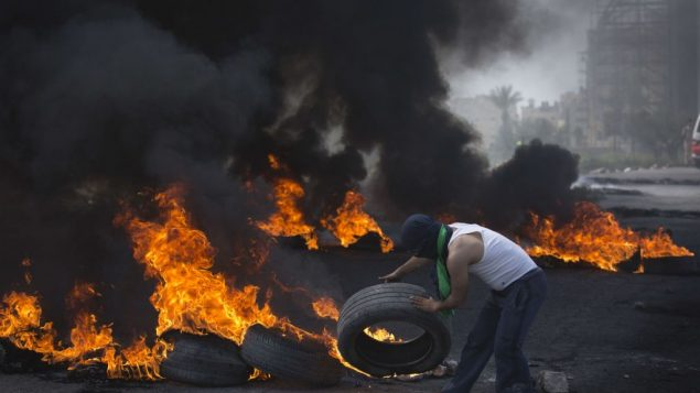 A Palestinian protester throws a tire into a pile of burning tires during clashes with Israeli border police, in the West Bank city of Ramallah, Friday, April 6, 2018. (AP Photo/Nasser Nasser)