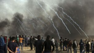 Israeli troops fire teargas at Palestinians during a protest at the Gaza Strip's border with Israel, Friday, April 13, 2018. (AP Photo/ Khalil Hamra)