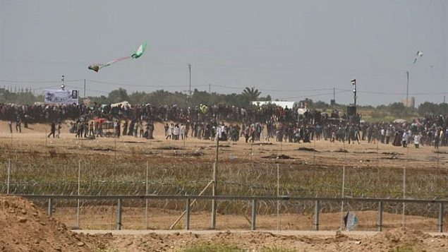 Palestinians try to use a kite to fly a Molotov Cocktail toward IDF troops along the Gaza fence on April 13 2018. (Israel Defense Forces)