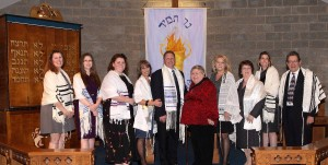 Congregation Ner Tamid's b'nai mitzvah class: Julie Segal (L-R), Julie Berenson, Rebecca Sussman, Kim Epstein, Jeff Epstein, Gail Teren, Kristine Goldstein, Susan Goldstein and Nicole Moseson – stand at the bimah with their teacher, Rabbi Thomas P. Liebschutz. PHOTO/courtesy Kim Epstein