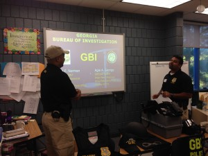 GBI Special Agents David Norman (left) and Agie George meet with students at GHA to detail the work they do as investigators.