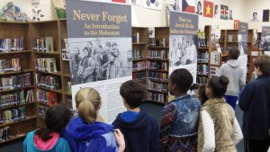 "Students at Renfroe Middle School in Decatur view ""Never Forget: An Introduction to the Holocaust,"" a traveling exhibit from Kennesaw State University's Museum of History and Holocaust Education. It shares the story of Norbert Friedman, a Sandy Springs resident who was born in Poland and survived 11 concentration camps. (Photo courtesy of City Schools of Decatur)"