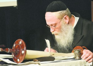 Rabbi Moshe Klein, shown during the March completion of a Torah for Chabad of Cobb, leads a team of seven sofrim (scribes) at eSofer.com.
