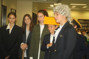 Forming the Georgia delegation, (from left) Max Murray as Butting Gwinnett, Sarah McMahon as Lyman Hall, and Phillip Weinstein as George Walton discuss how to raise a militia for the Revolutionary War.